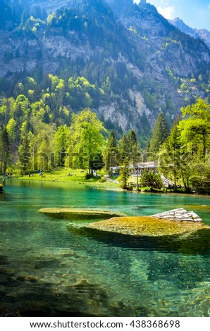 Spring time at Romantic forest lake, Blausee. One of the best-known mountain lakes in Switzerland. Beautiful crystal-clear color water with green tree around the lake.