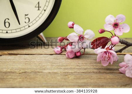 Spring Time Change / Pink Blossoms and an Alarm Clock on an Old Wooden Table - stock photo
