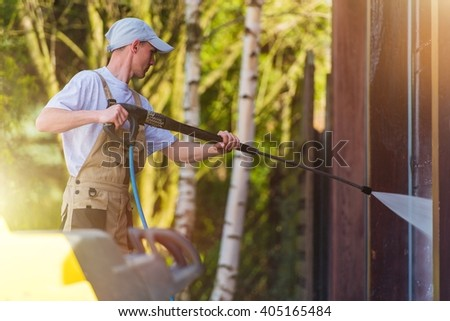 Spring Time House Walls Cleaning by High Pressure Water Spraying. Caucasian Men at Work. - stock photo
