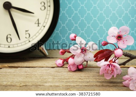 Spring Time / Pink Blossoms and an Alarm Clock on an Old Wooden Table - stock photo