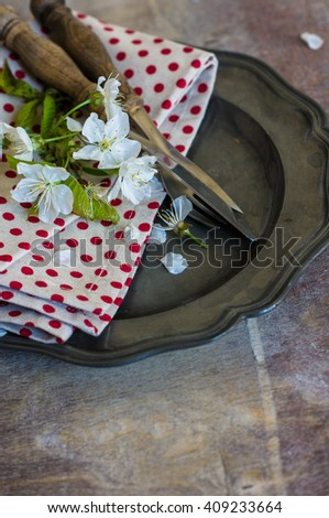 Spring time table setting with cherry blossom and vintage silverware on rustic background
