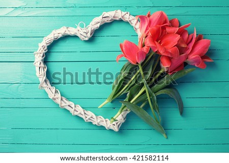 Spring tulips and   big white decorative heart  on aquamarine  painted wooden background. Selective focus. Place for text. Toned image. - stock photo