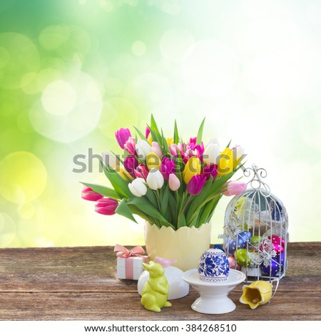 Spring tulips with easter egg and bunny on table over green garden background - stock photo