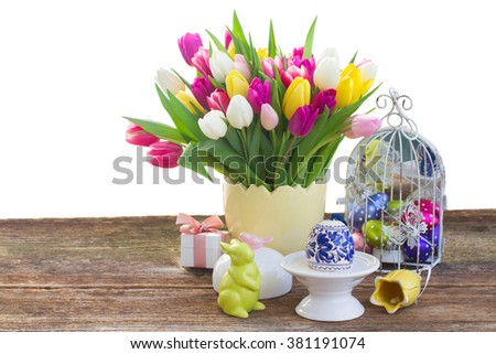 Spring tulips with easter egg and bunny on table over white background