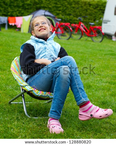 Spring vacation in camping - Cute girl resting in the colorful recliner - stock photo