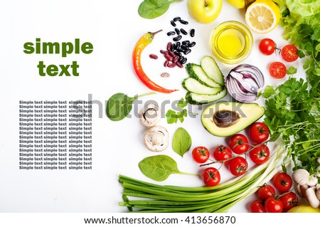 Spring vegetable background. Juicy fresh spring vegetables and herbs, such as cherry tomatoes, lettuce, spinach, cucumber slices and stuff on a white background. Place for writing text (left) - stock photo