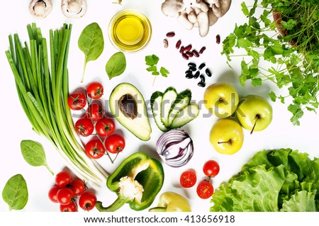 Spring vegetable background. Juicy fresh spring vegetables and herbs, such as cherry tomatoes, lettuce, spinach, cucumber slices and stuff on a white background.  - stock photo