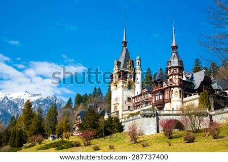 Spring view of Peles Castle with snow Bucegi Mountains in the background. - stock photo