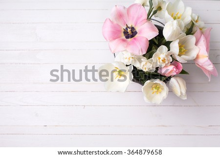 Spring white and pink  tulips and narcissus on white painted wooden background. Selective focus. Place for text.  - stock photo