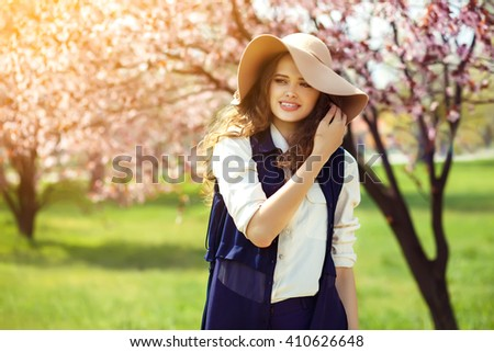 Spring woman in green garden enjoying the sunny day. beautiful clothes. a great hat. blurred background. spring park