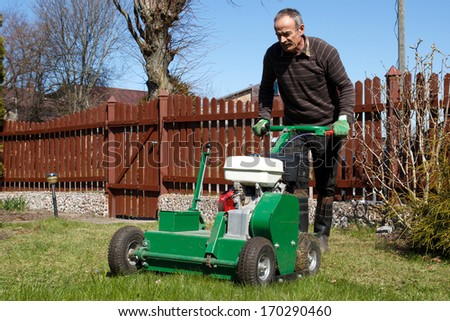 Spring work in garden. Man work with Man working with Lawn Aerator - stock photo