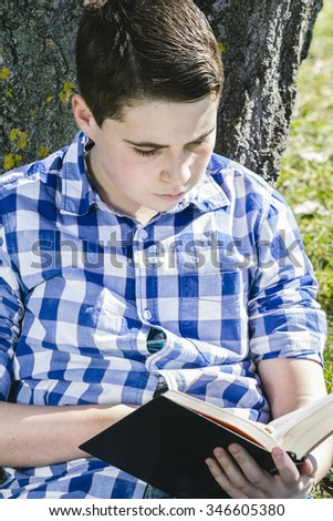 Spring Young boy reading a book in the woods with shallow depth of field and copy space - stock photo