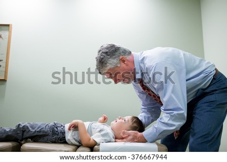 SPRINGFIELD, OR - AUGUST 20, 2014: Chiropractor adjusting the spine of a young boy in a doctor's office room. - stock photo