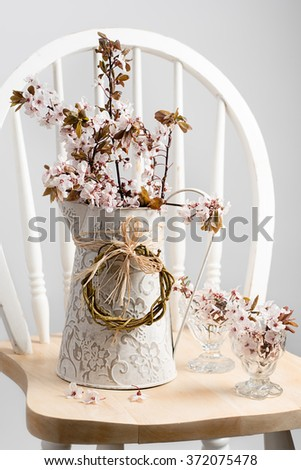 Springtime cherry blossom in decorative jug sitting on chair - stock photo