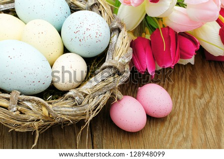 Springtime Easter nest with eggs and flowers over a wood background