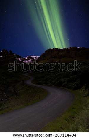Springtime Northern Lights  over winding valley road, Iceland - stock photo