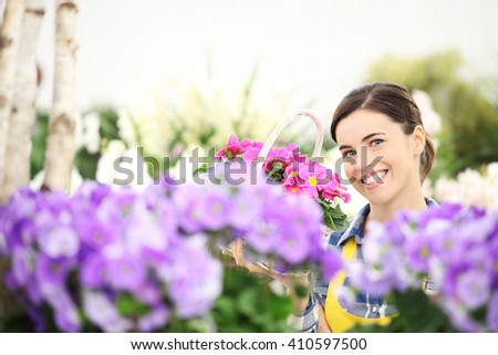 springtime, woman smiling with white wicker basket flowers of purple primroses