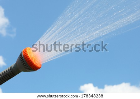 sprinkle spraying the water over the blue background - stock photo