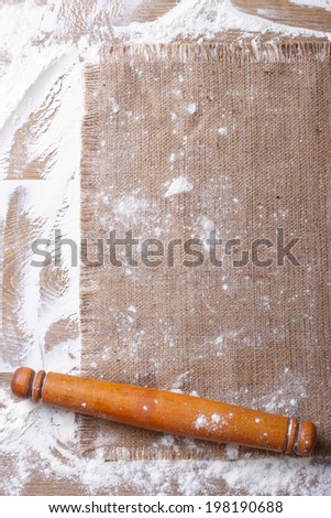 Sprinkled flour and rolling pin on a wooden board and burlap vertical close up  - stock photo