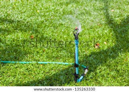 sprinkler head dispersing water on grass - stock photo