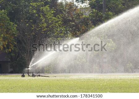 sprinkler head watering the grass - stock photo
