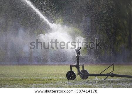 sprinkler head watering the grass in sport field. - stock photo