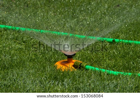 Sprinkler splashes water on grassland