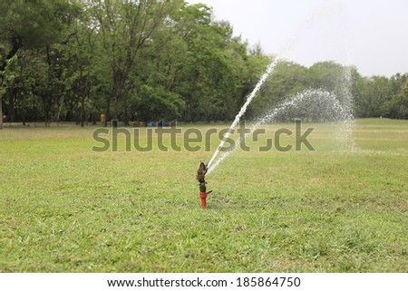 Sprinkler spraying water over green grass.
