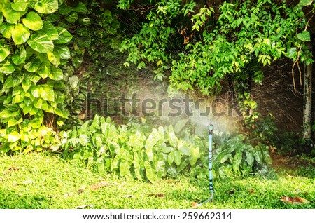 sprinkler watering grass - stock photo
