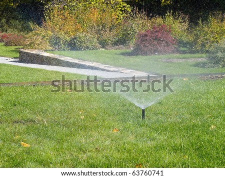 Sprinkler Watering lawn on a sunny autumn day - stock photo