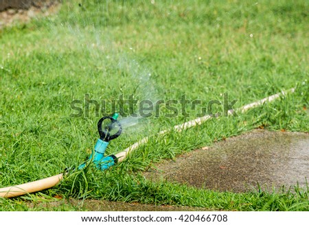 Sprinkler watering On the background of grass - stock photo
