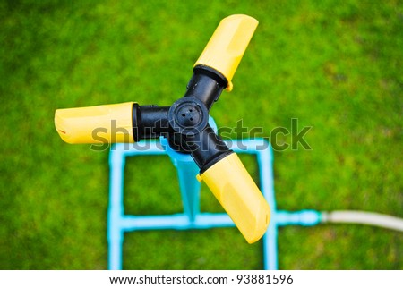 Sprinkler watering the grass in the park - stock photo