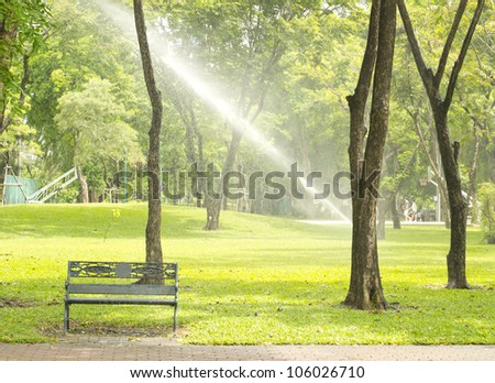 Sprinkler watering the green grass and bench on a sunny summer day in public park - stock photo