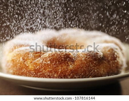 Sprinkling a crown cake with sugar - stock photo
