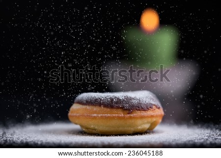 Sprinkling sugar on delicious donut topped with chocolate. Romantic atmosphere and candle in background. Shallow depth of field. - stock photo