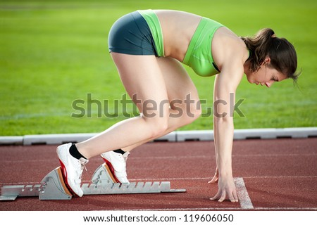 Sprinter in the starting blocks, ready to go - stock photo