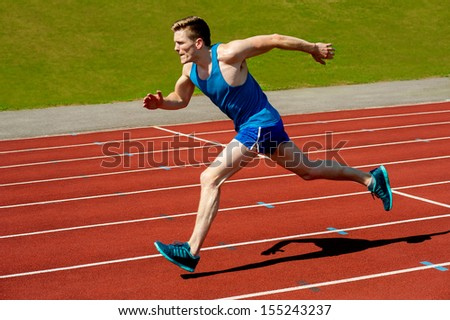 Sprinter leaving starting blocks on running track