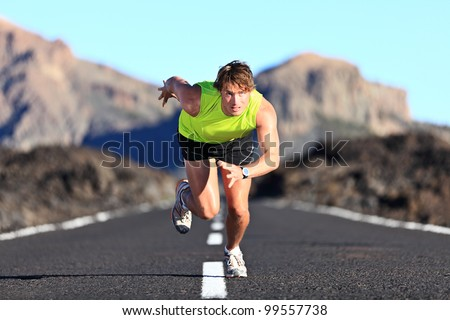 Sprinter. Man running on road at high speed in beautiful exotic mountain landscape. Male athlete runner in intense sprint during outdoor workout - stock photo