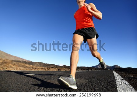 Sprinting running man - male runner training outdoors jogging on mountain road in amazing landscape nature. Close up of fit handsome jogger working out for marathon outside in summer. - stock photo