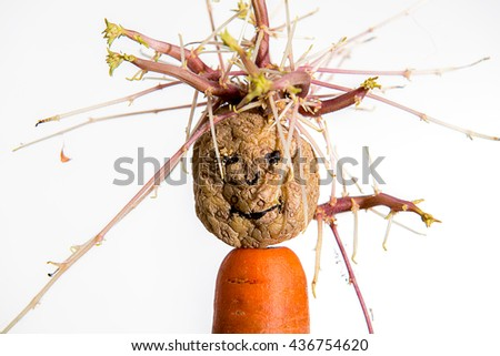 sprouting potato- face on carrot in front of white background - stock photo