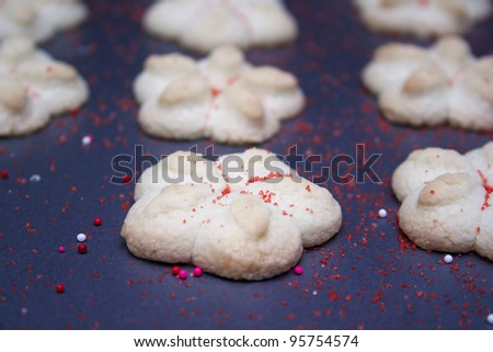 Sprtiz cookies with red sugar on a cookie sheet. - stock photo