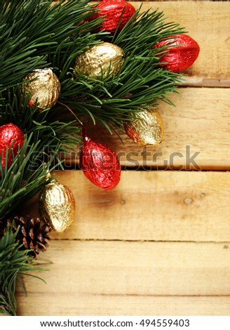 spruce branches and chocolates in shiny wrapper on a wooden plank background.  vertical