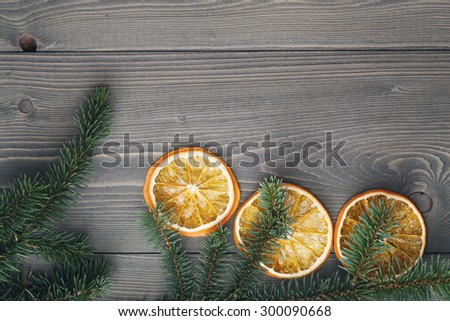 spruce twig with dried orange slices on old table, vintage toned photo - stock photo