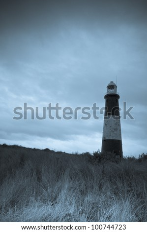 Spurn Head Lighthouse - this is a selenium toned monochrome image. The mood is gloomy and the sky is ominous in the background, providing ample space for copy if required.