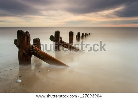 Spurn Point sea breakers (groynes) at dawn, East Yorkshire - stock photo