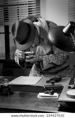 Spy agent stealing top secret data and taking pictures, 1950s style office. - stock photo