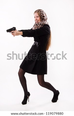 Spy girl in a black coat shoots a gun