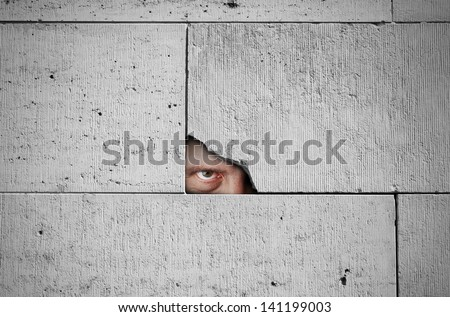 Spy is watching through a hole in the wall