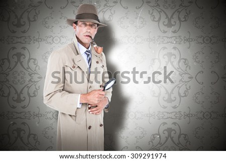 Spy looking through magnifier against elegant patterned wallpaper in grey tones - stock photo