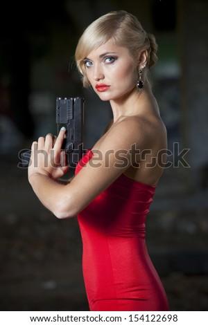Spy woman in retro look holding a gun - stock photo
